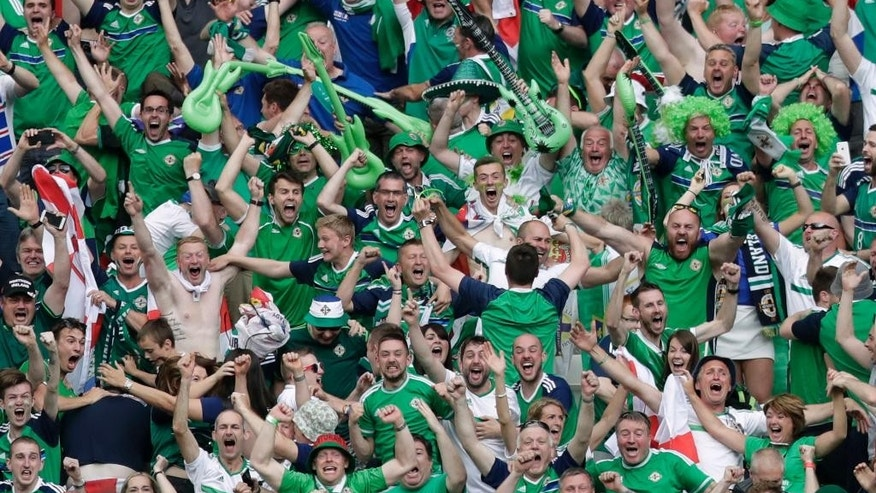 Northern Ireland supporters celebrate their side's second goal during the Euro 2016 Group C soccer match between Ukraine and Northern Ireland at the Grand Stade in Decines-­Charpieu, near Lyon, France, Thursday, June 16, 2016. (AP Photo/Pavel Golovkin)