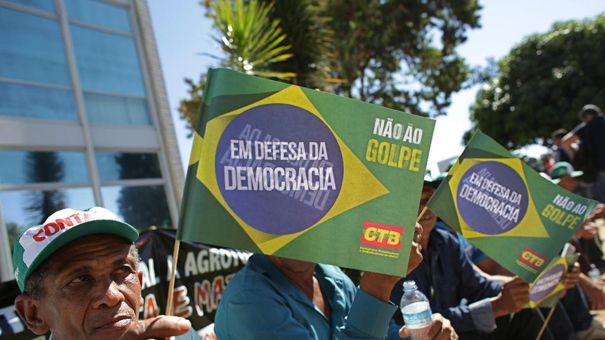 "Farmers hold signs that read in Portuguese ""In Defense of Democracy. Not to the coup"" during a protest against the government of acting President Michel Temer in Brasilia, Brazil, Thursday, June 16, 2016. Farmers say they fear Temer will end social programs and halt agrarian reform that was underway under suspended President Dilma Rousseff. (AP Photo/Eraldo Peres)"