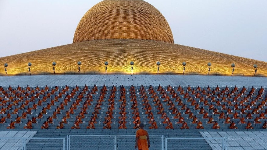 FILE - In this Feb. 22, 2016 file photo, Thai Buddhist monks gather at the gates of the main temple of Wat Dhammakaya to participate in Makha Bucha Day ceremonies in Pathum Thani, Thailand. Scandals have cast a spotlight on misbehaving monks and given rise to reflection on the state of Buddhism in Thailand, which is the national religion. (AP Photo/Sakchai Lalit, File)
