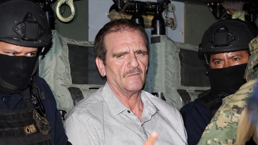 "This photo provided by the Mexican Attorney General's Office shows Hector ""El Guero"" Palma sitting between federal police inside a helicopter at a federal hanger in Mexico City,  Wednesday, June 15, 2016. Palma, one of the founders of the Sinaloa Cartel, returned to his native Mexico after serving almost a decade in a U.S. prison and was immediately transported to another maximum-security lockup where he will await trial for two murders. (Mexico's Attorney General's Office via AP)"