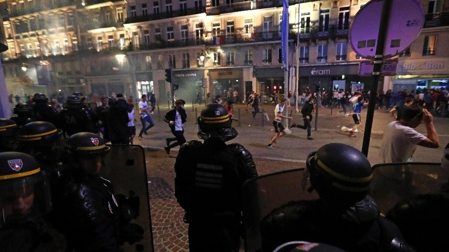 People run after police fired tear gas in downtown Lille, France Wednesday, June 15, 2016 during clashes one day ahead of the Euro 2016 Group B soccer match against Wales in nearby Lens.  (AP Photo/Darko Bandic)