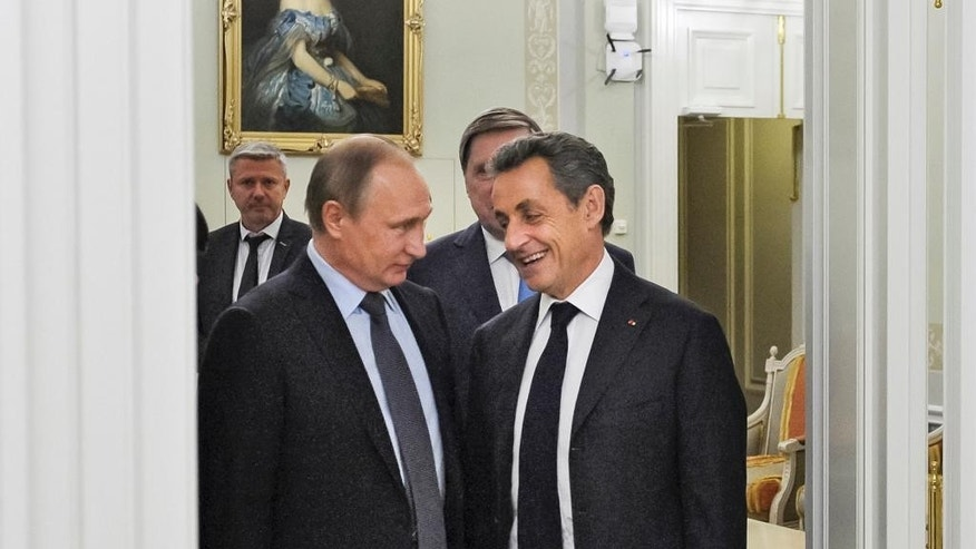 Russian President Vladimir Putin, left, and former French President Nicolas Sarkozy speak to each other during their meeting on the eve of the St. Petersburg International Investment Forum, in Russia, Wednesday, June 15, 2016. (Mikhail Klimentyev, Sputnik, Kremlin Pool Photo via AP)