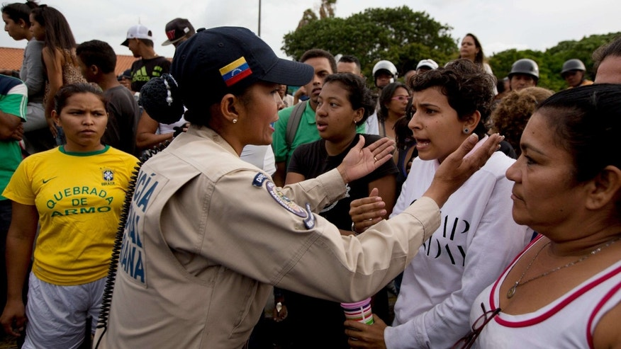 June 14, 2016: A police officer talks to an angry crowd during a protest for food at the Catia neighborhood in Caracas, Venezuela.