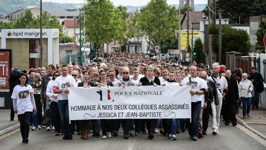 "Police officers and residents walk with a banner reading ""Homage to the two slain colleagues Jessica and Jean-Baptiste"" during a white march in Mantes-la-Jolie, west of Paris, Thursday, June 16, 2016. French police officials Jean-Baptiste Salvaing and his companion Jessica Schneider were killed Monday by an Islamic State extremist. (AP Photo/Kamil Zihnioglu)"