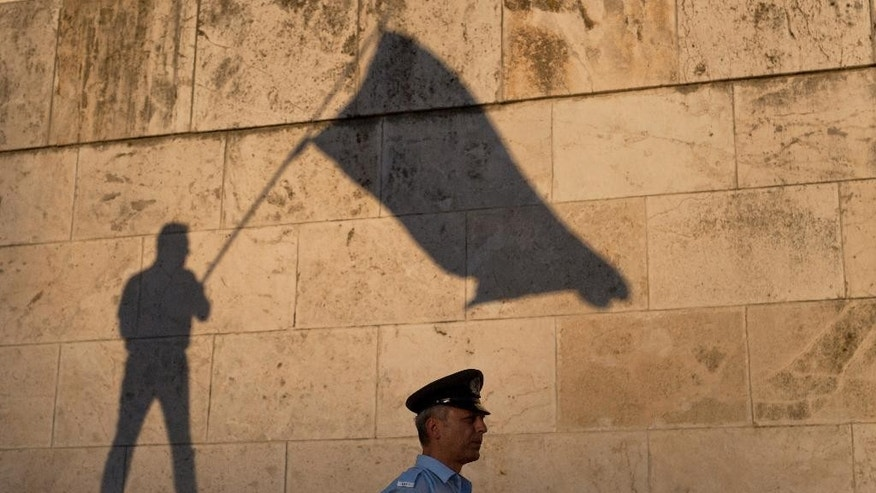 The shadow of a demonstrator waving a flag is cast on a wall as a Greek police officer secures the Greek Parliament during a protest in central Athens, Wednesday, June 15, 2016. Several thousand anti-government protesters gathered in central Athens Wednesday to demand the resignation Prime Minister Alexis Tsipras, accusing his government of breaking promises to end austerity and sinking the country deeper into financial distress.(AP Photo/Petros Giannakouris)