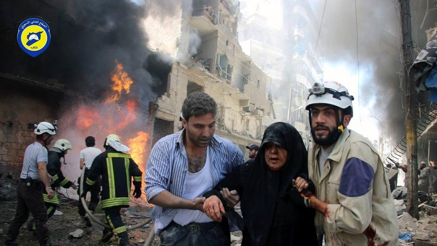 In this photo taken on June 8, 2016 provided by the Syrian Civil Defense Directorate in Liberated Province of Aleppo, which has been authenticated based on its contents and other AP reporting, shows Syrian civil defense workers, right, helps an injured woman after warplanes attacked a street, in Aleppo, Syria. After four years of grinding battles, Aleppo's divided residents face a common fear as the prospect of a total siege looms. Syria's largest city used to be its economic locomotive, now it is has become an emblem of its stalemated civil war. (Civil Defense Directorate in Liberated Province of Aleppo via AP)