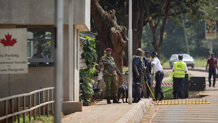 Armed Kenyan police and private security guard the entrance to the Canadian High Commission after a bomb scare in Nairobi, Kenya Thursday, June 16, 2016. Kenya's police chief says a large package sent to the Canadian High Commission in Nairobi caused police to seal off roads as Kenyan bomb experts inspected the package, which turned out to contain visa application forms. (AP Photo/Ben Curtis)