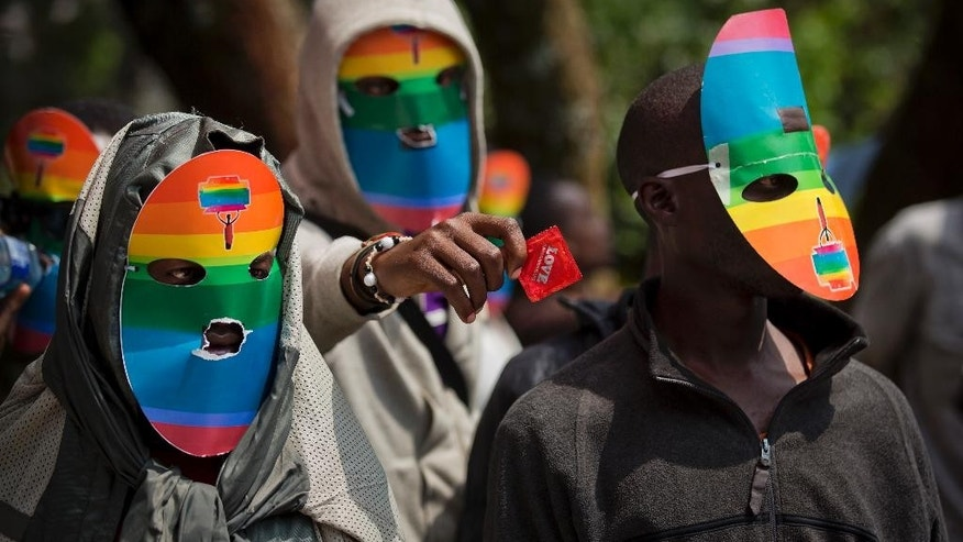 FILE - In this Monday, Feb. 10, 2014 file photo, Kenyan gays and lesbians and others supporting their cause wear masks to preserve their anonymity and one holds out a wrapped condom, as they stage a rare protest, against Uganda's increasingly tough stance against homosexuality and in solidarity with their counterparts there, outside the Uganda High Commission in Nairobi, Kenya. A Kenyan judge on Thursday, June 16, 2016 has upheld the use of enforced anal examinations to determine a suspect's sexual orientation, saying he found no violation of rights or the law and dismissed the petition by two men who were subjected to the procedures. (AP Photo/Ben Curtis, File)