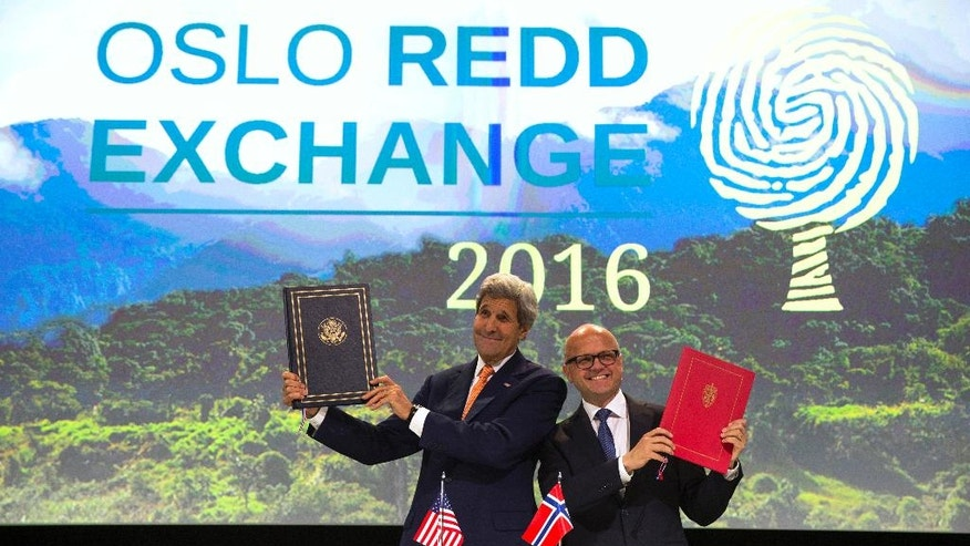 Secretary of State John Kerry and Norwegian Minister of Climate and Environment Vidar Helgesen hold up an agreement between the two countries to enhance collaboration to fight deforestation and climate change, during the Oslo REDD Exchange conference, Wednesday, June 15, 2016, in Oslo. (AP Photo/Evan Vucci, Pool)