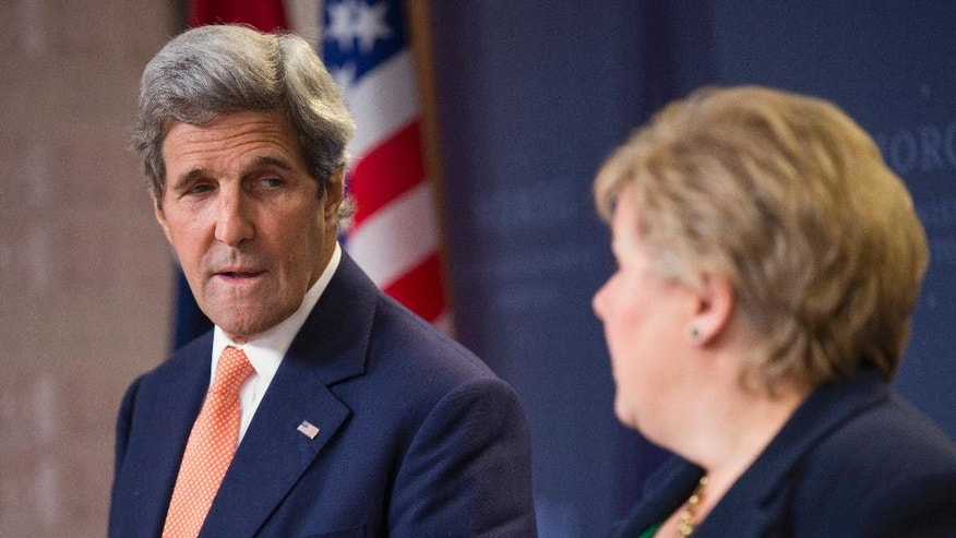 U.S. Secretary of State John Kerry, left, looks on as Norwegian Prime Minister Erna Solberg speaks during a news conference, Wednesday, June 15, 2016, in Oslo. (AP Photo/Evan Vucci, Pool)