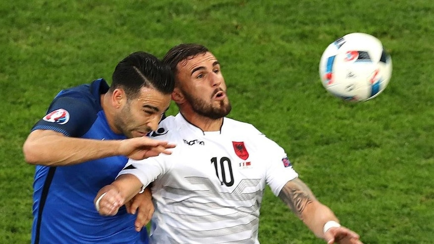 Albania's Armando Sadiku fights for the ball against France's Adil Rami during the Euro 2016 Group A soccer match between France and Albania at the Velodrome stadium in Marseille, France, Wednesday, June 15, 2016. (AP Photo/Claude Paris)