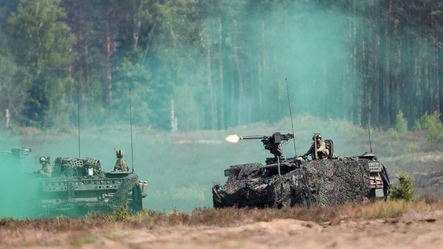 Members of the U.S. Army take part in a military exercise 'Iron Wolf 2016' at the Training Range in Pabrade some 60km.(38 miles) north of the capital Vilnius,, Lithuania, Thursday, June 16, 2016. Iron Wolf 2016, the part of the annual multinational Exercise Saber Strike held in Lithuania, is running in June in Rukla and Pabrade, two training areas of the Lithuanian Armed Forces. In total, over 5 thousand soldiers from 7 NATO allies are training at the same time in Lithuania this year. (AP Photo/Mindaugas Kulbis)