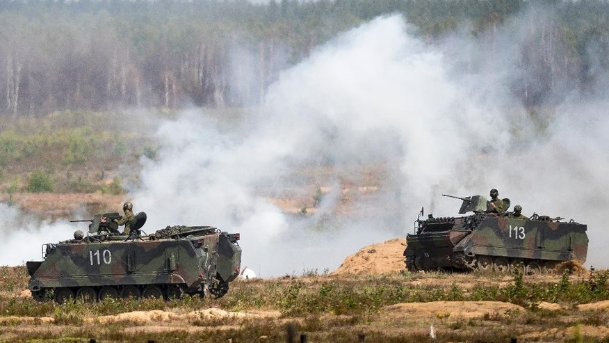 Soldiers from NATO countries attend an military exercise 'Iron Wolf 2016' at the Training Range in Pabrade some 60km.(38 miles) north of the capital Vilnius, Lithuania, Thursday, June 16, 2016. Iron Wolf 2016, the part of the annual multinational Exercise Saber Strike held in Lithuania, is running in June in Rukla and Pabrade, two training areas of the Lithuanian Armed Forces. In total, over 5 thousand soldiers from 7 NATO allies are training at the same time in Lithuania this year. (AP Photo/Mindaugas Kulbis)