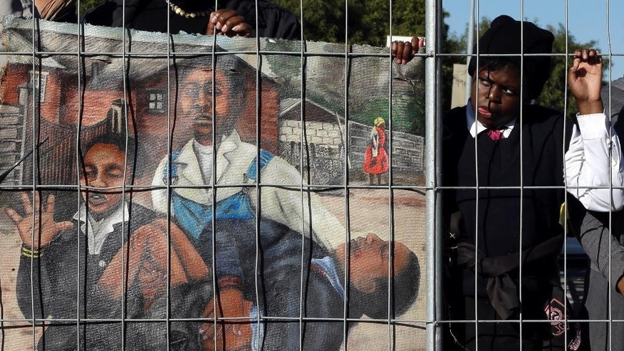 A young girl watches the laying of the wreath ceremony, at the Hector Pieterson Memorial, in Soweto, South Africa, Thursday, June 16, 2016, near to a painting depicting the iconic photo showing 13-year-old Hector Pieterson, being carried after being shot by police during the 1976 Soweto uprising, displayed by an artist for commemoration of the 40th anniversary of uprisings. South Africans are commemorating the 40th anniversary of a pivotal moment in the anti-apartheid struggle, a 1976 black student uprising in the Soweto area of Johannesburg that led to a deadly crackdown but launched a new phase of opposition to white minority rule. (AP Photo/Themba Hadebe)
