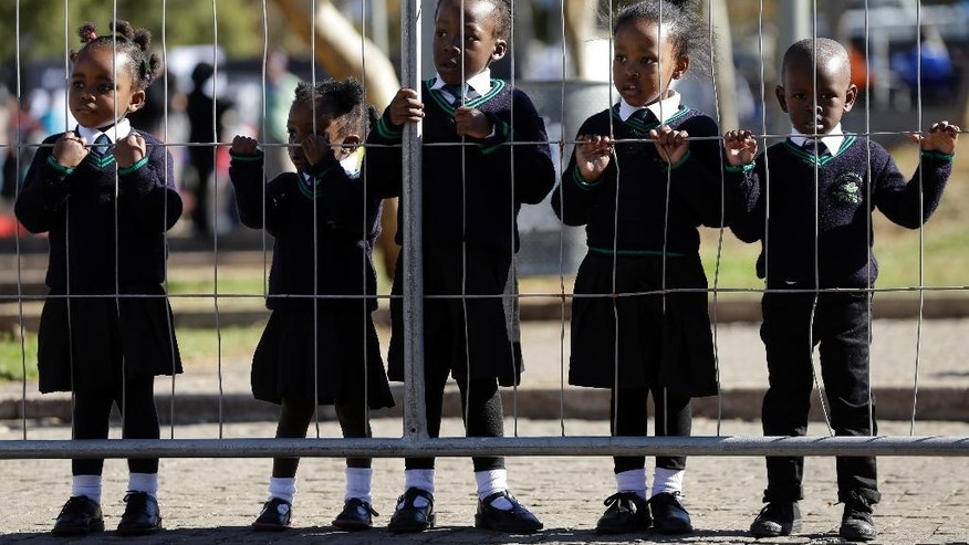 Children wearing school uniforms watch the laying of wreaths, at the Hector Pieterson Memorial in Soweto, South Africa, Thursday, June 16, 2016, for commemoration of the 40th anniversary of uprisings. South Africans are commemorating the 40th anniversary of a pivotal moment in the anti-apartheid struggle, a 1976 black student uprising in the Soweto area of Johannesburg that led to a deadly crackdown but launched a new phase of opposition to white minority rule. (AP Photo/Themba Hadebe)