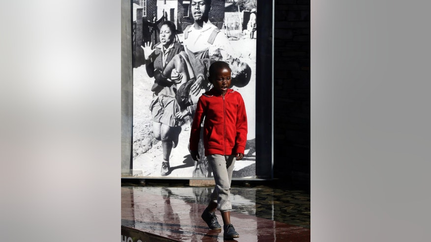 A young boy walks way from a displayed iconic photo showing 13-year-old Hector Pieterson, being carried after being shot by police during the 1976 Soweto uprising,at the Hector Pieterson Memorial in Soweto, South Africa, Thursday, June 16, 2016, for the commemoration of the 40th anniversary of uprisings. South Africans are commemorating the 40th anniversary of a pivotal moment in the anti-apartheid struggle, a 1976 black student uprising in the Soweto area of Johannesburg that led to a deadly crackdown but launched a new phase of opposition to white minority rule. (AP Photo/Themba Hadebe)