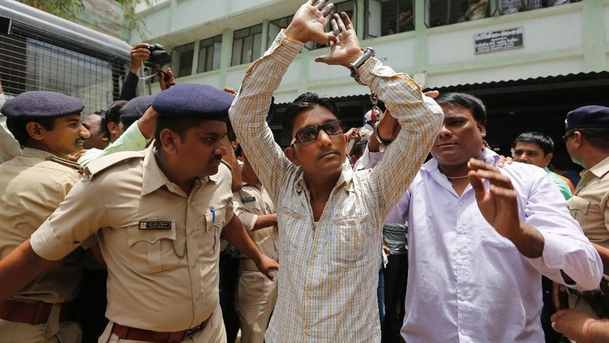 An Indian man convicted for the 2002 Gujarat riots is taken back to jail after the court announced the lengths of the sentences in Ahmadabad, India, Friday, June 17, 2016. An Indian court has sentenced 11 people to life in prison for murder in one of the many deadly religious riots that swept across the western state of Gujarat in 2002, leaving more than 1,000 dead. Special Court Judge P. B. Desai on Friday rejected the demand for death penalty as the prosecution failed to prove charges of criminal conspiracy against the defendants. The judge also sentenced 12 defendants to seven years in prison and one to 10 years in prison in the case. (AP Photo/Ajit Solanki)