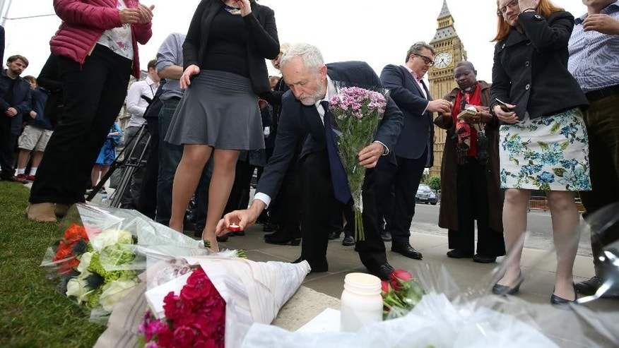 Labour Party leader Jeremy Corbyn, centre, lays a candle as he and deputy leader Tom Watson, centre rear, Thursday June 16, 2016, attend an impromptu vigil at Parliament Square opposite the Palace of Westminster, central London, following the death of Labour Member of Parliament, Jo Cox. The British lawmaker who campaigned for the country to stay in the European Union was killed Thursday by a gun- and knife-wielding attacker in her small-town constituency, a tragedy that brought the country's fierce, divisive referendum campaign to a shocked standstill. (Philip Toscano/PA via AP)  UNITED KINGDOM OUT