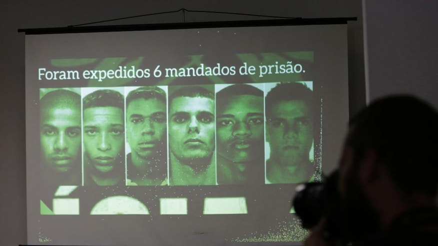 Photos of gang rape suspects are displayed on a screen during a press conference in Rio de Janeiro, Brazil, Friday, June 17, 2016. The police officer investigating the gang rape of a 16-year-old girl that made international headlines because videos showing men posing with the unconscious victim were shared on social media says she's asking charges be brought against six men and a minor. (AP Photo/Silvia Izquierdo)