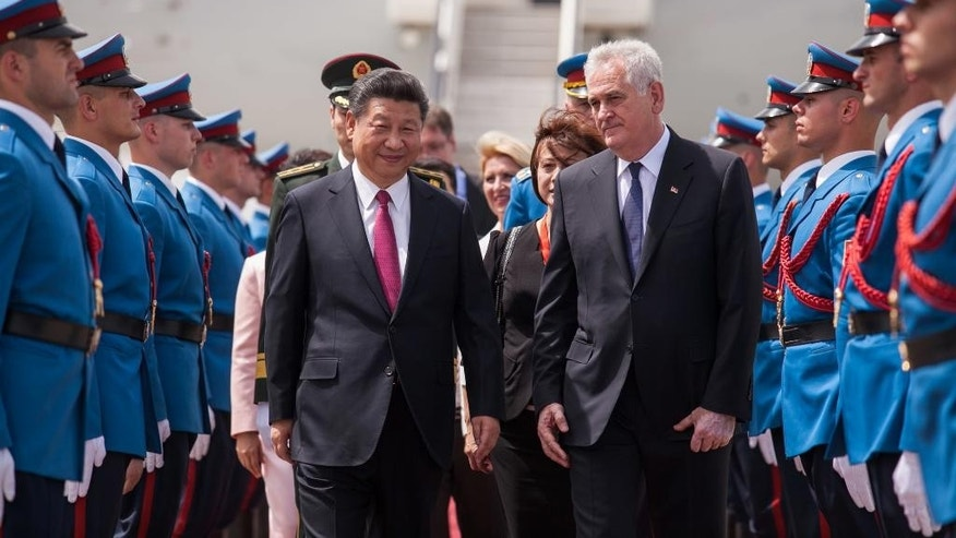 In this photo provided by the Serbian Presidential Press Service, Chinese President Xi Jinping, center left, and his Serbian counterpart, Tomislav Nikolic, center right, pass by Serbian army Honor Guards upon Xi's arrival to Belgrade, Serbia, Friday, June 17, 2016. Xi arrived in Serbia on Friday for a visit meant to boost relations with the friendly nation and assert China's intention to increase its presence in the Balkans and Europe. (Serbian Presidential Press Service via AP)