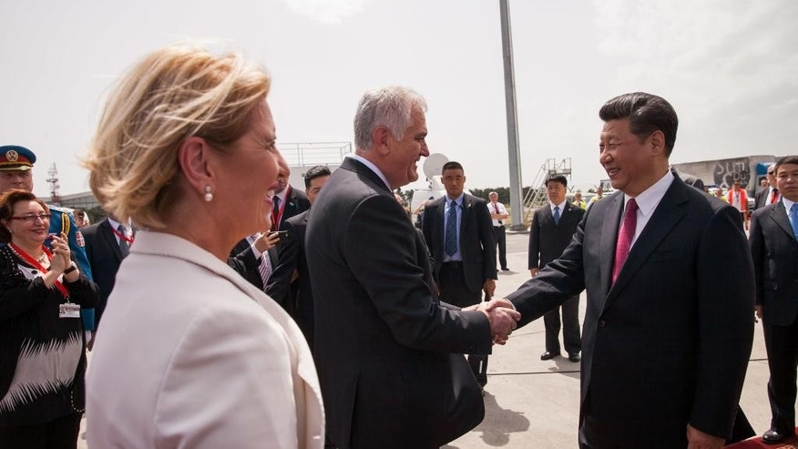 In this photo provided by the Serbian Presidential Press Service, Chinese President Xi Jinping, right, and his Serbian counterpart, Tomislav Nikolic, center, shake hands upon Xi's arrival to Belgrade, Serbia, Friday, June 17, 2016. Xi arrived in Serbia on Friday for a visit meant to boost relations with the friendly nation and assert China's intention to increase its presence in the Balkans and Europe. (Serbian Presidential Press Service via AP)