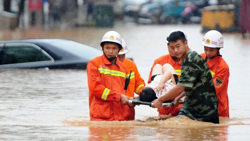 In this June 15, 2016 photo, rescuers carry a woman on a stretcher through a flooded area in Jiujiang in southern China's Jiangxi province. A week of torrential rain in southern China has killed dozens people and displaced tens of thousands of residents, including many in China's poor, remote regions. (Chinatopix via AP) CHINA OUT
