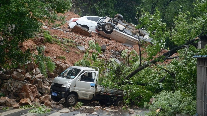In this June 15, 2016 photo, damaged vehicles are stuck on a section of road blocked by a landslide in Zhuzhou in southern China's Hunan province. A week of torrential rain in southern China has killed dozens of people and displaced tens of thousands of residents, including many in China's poor, remote regions. (Chinatopix via AP) CHINA OUT