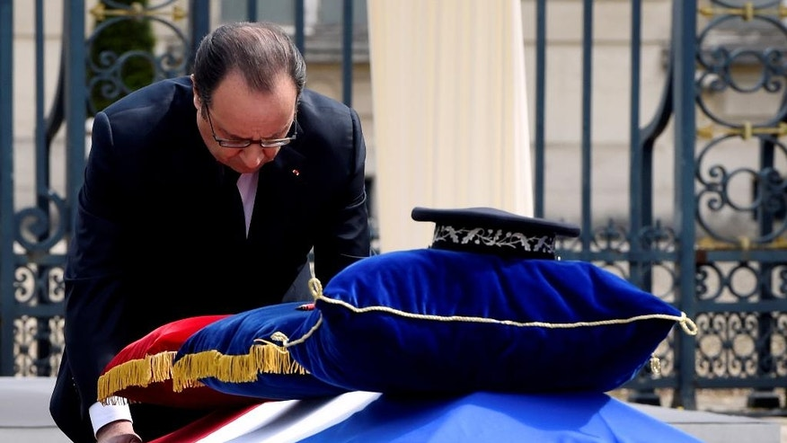 French President Francois Hollande pays his respects at the coffin of one the two police officials killed.