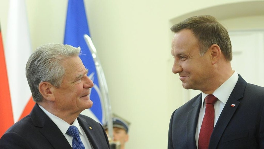 German President Joachim Gauck, left, is welcomed by his Polish counterpart Andrzej Duda, right, at the presidential palace in Warsaw, Poland, Friday, June 17, 2016. Gauck came to Poland for celebrations of the 25th anniversary of the Polish-German treaty on good-neighborly relations. (AP Photo/Alik Keplicz)