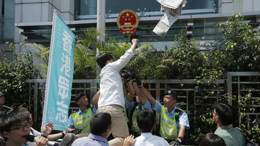 Oscar Lai, a member of pro-democracy group Demosisto, throws a newspaper reporting Hong Kong bookseller Lam Wing-Kee into the Chinese central government's liaison office in Hong Kong, Friday, June 17, 2016. Lam, one of the five Hong Kong booksellers whose disappearances sparked international concern, said Thursday he spent months confined in a room under constant surveillance by mainland Chinese authorities, who interrogated him about his publishing company's authors and customers. (AP Photo/Kin Cheung)
