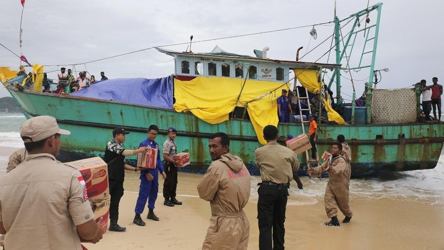 Indonesian officials load food supplies onto a boat carrying Tamil migrants which have been stranded on the beach for the last few days in Lhoknga, Aceh province, Indonesia, Friday, June 17, 2016. Authorities are preparing to tow the boat carryingvdozens of men, women and children out to sea Friday after rescuing it last weekend. (AP Photo/Heri Juanda)
