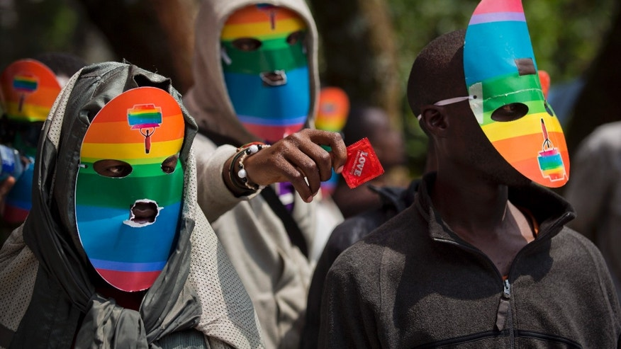 FILE - In this Monday, Feb. 10, 2014 file photo, Kenyan gays and lesbians and others supporting their cause wear masks to preserve their anonymity and one holds out a wrapped condom, as they stage a rare protest, against Uganda's increasingly tough stance against homosexuality and in solidarity with their counterparts there, outside the Uganda High Commission in Nairobi, Kenya.