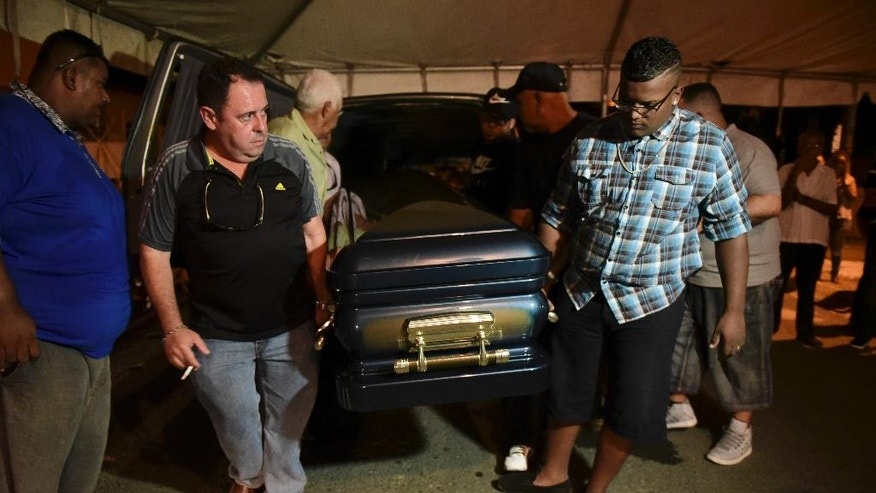 Friends and family bring in the coffin containing the body of Angel Candelario Padro, one of the 23 Puerto ricans that died at the hands of a gunman in Orlando, Florida last Sunday, in Guanica, Puerto Rico, Thursday, June 16, 2016. Dozens of people where gunned down at the nightclub, making it the deadliest mass shooting in modern U.S. history. (AP Photo/Carlos Giusti)