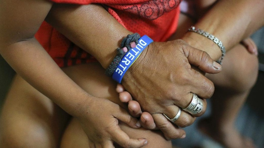 "In this Wednesday June 8, 2016 photo, a Filipino street dweller wearing a rubber bracelet bearing the name of Philippine President-elect Rodrigo Duterte sits inside a police station with her son after their arrest for violating the night curfew in Manila, Philippines. In a crackdown,  dubbed ""Oplan Rody,"" bearing Duterte's name, police rounded up hundreds of children or their parents to enforce a night curfew for minors, and taken away drunk and shirtless men roaming metropolitan Manila's slums. The poor, who were among Duterte's strongest supporters, are getting a foretaste of the war against crime he has vowed to wage. (AP Photo/Aaron Favila)"