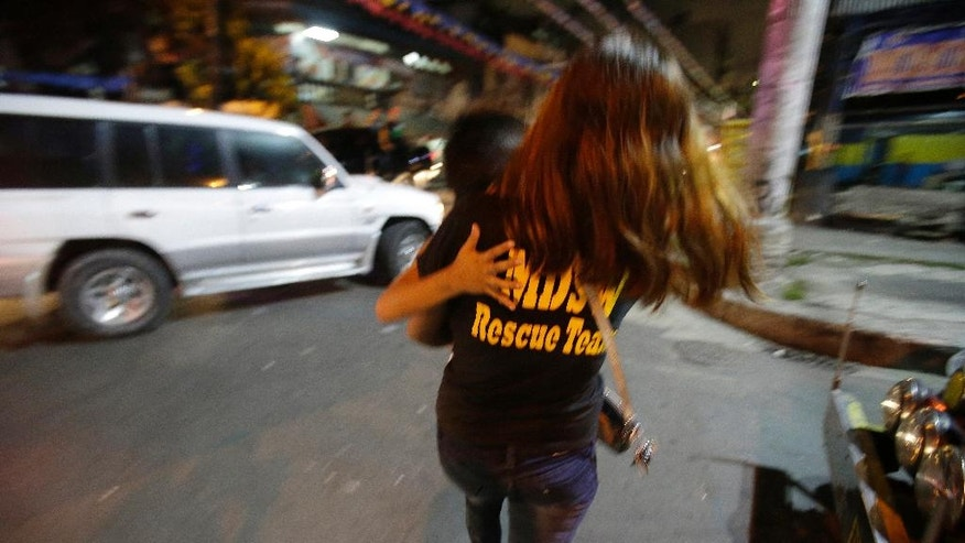 "In this Wednesday June 8, 2016 photo, a Filipino social worker carries a boy she apprehended as they enforce a night to dawn curfew for minors in Manila, Philippines. In a crackdown, dubbed ""Oplan Rody,"" bearing Duterte's name, police rounded up hundreds of children or their parents to enforce a night curfew for minors, and taken away drunk and shirtless men roaming metropolitan Manila's slums. The poor, who were among Duterte's strongest supporters, are getting a foretaste of the war against crime he has vowed to wage. (AP Photo/Aaron Favila) (AP Photo/Aaron Favila)"