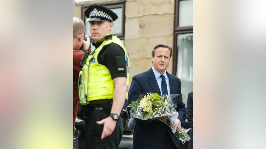 Britain's Prime Minister David Cameron prepares to lay a floral tribute in Birstall, northern England, for Jo Cox, the 41-year-old British Member of Parliament shot to death in northern England, Friday June 17, 2016. The mother of two young children was shot to death Thursday afternoon in her constituency near Leeds. A 52-year-old man has been arrested but has not been charged. (Danny Lawson/PA via AP) UNITED KINGDOM OUT