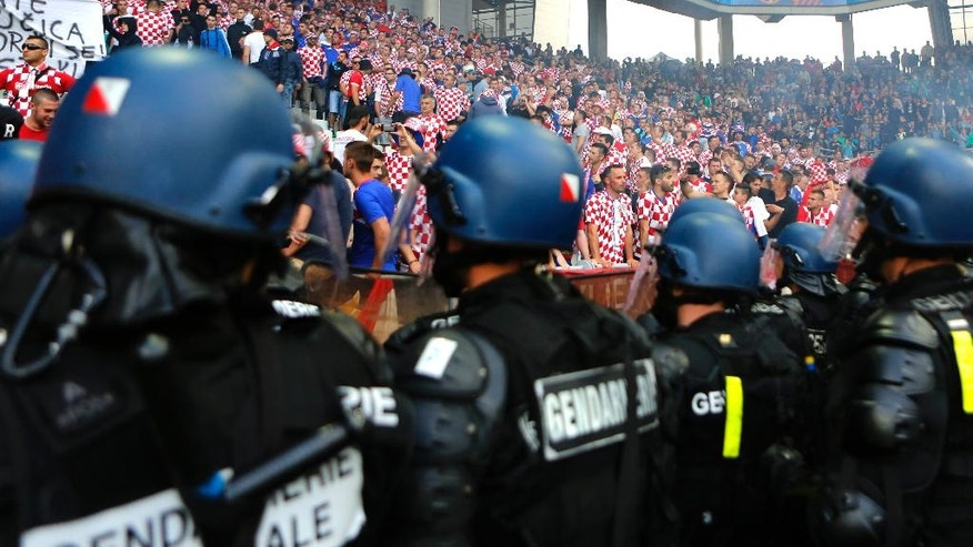 French police officers watch the Croatian fans after flares were thrown onto the pitch during the Euro 2016 Group D soccer match between the Czech Republic and Croatia at the Geoffroy Guichard stadium in Saint-Etienne, France, Friday, June 17, 2016. (AP Photo/Darko Bandic)