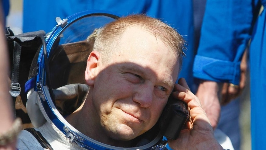 Member of the International Space Station (ISS) crew Tim Kopra of US speaks on a satellite phone shortly after landing near the town of Dzhezkazgan, Kazakhstan, Saturday, June 18, 2016. A three-person crew from the International Space Station has landed safely in the sun-drenched steppes of Kazakhstan. (Shamil Zhumatov/Pool Photo via AP)