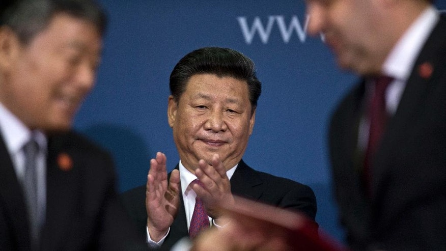 Xi Jinping, China's President, center, applauds during a ceremony in Belgrade, Serbia, Saturday, June 18, 2016. Xi arrived in Serbia for a visit meant to boost relations with the friendly nation and assert China's intention to increase its presence in the Balkans and Europe. (AP Photo/Marko Drobnjakovic)