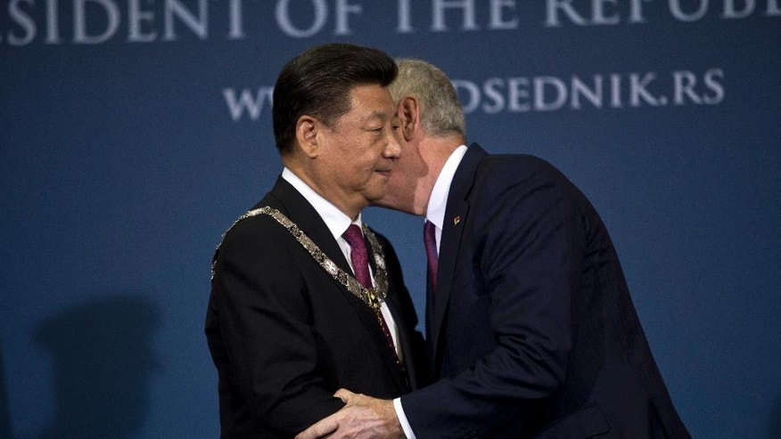 Xi Jinping, China's President, left, is congratulated by his Serbian counterpart, Tomislav Nikolic, after being presented with a state medal in Belgrade, Serbia, Saturday, June 18, 2016. Xi arrived in Serbia for a visit meant to boost relations with the friendly nation and assert China's intention to increase its presence in the Balkans and Europe. (AP Photo/Marko Drobnjakovic)