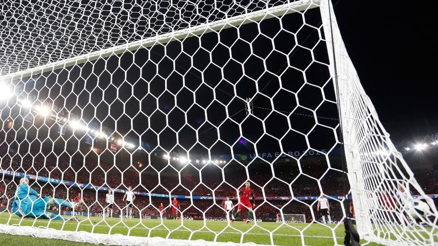 Austria goalkeeper Robert Almer, left, watches as Portugal's Cristiano Ronaldo, center, misses a penalty during the Euro 2016 Group F soccer match between Portugal and Austria at the Parc des Princes stadium in Paris, France, Saturday, June 18, 2016. (AP Photo/Martin Meissner)