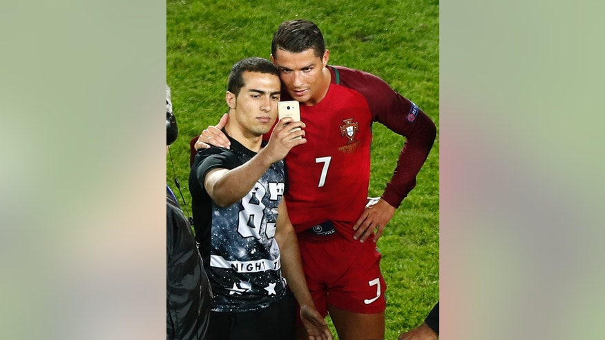 Portugal's Cristiano Ronaldo poses for a selfie with a man who invaded the pitch at the end of the Euro 2016 Group F soccer match between Portugal and Austria at the Parc des Princes stadium in Paris, France, Saturday, June 18, 2016. (AP Photo/Francois Mori)