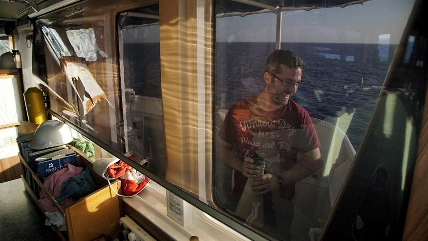 """Andreas Tsigkanas, who is first mate on board the """"Aquarius"""", jokes around with colleagues at the ship while out on the Meditarranean sea, Wednesday, June 15, 2016. A total of seven humanitarian organizations work in the so-called 'Search and Rescue' (SAR) zone near the Libyan coast. The medical aid group Medecins Sans Frontieres (MSF) and the rescue group SOS Mediteranee work together on board the ship to rescue migrants and refugees from boats in distress in the Mediterranean. (AP Photo/Bram Janssen)"""