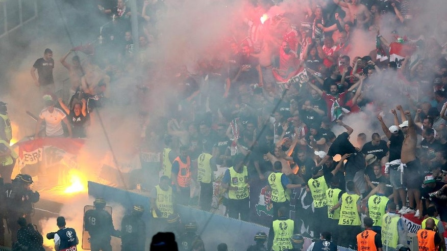 Supporters of Hungary light fireworks  during the Euro 2016 Group F soccer match between Iceland and Hungary at the Velodrome stadium in Marseille, France, Saturday, June 18, 2016. (AP Photo/Claude Paris)