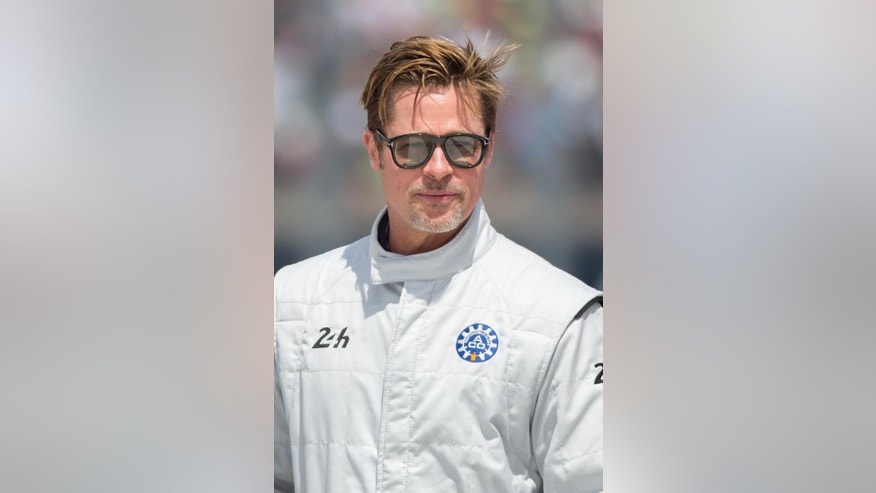 Actor Brad Pitt poses for photographs, prior to starting the 84th 24-hour Le Mans endurance race, in Le Mans, western France, Saturday, June 18, 2016. (AP Photo/Kamil Zihnioglu)