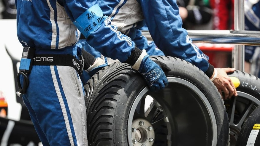 Mechanics work on a tire prior to the 84th 24-hour Le Mans endurance race, in Le Mans, western France, Saturday, June 18, 2016. (AP Photo/Kamil Zihnioglu)