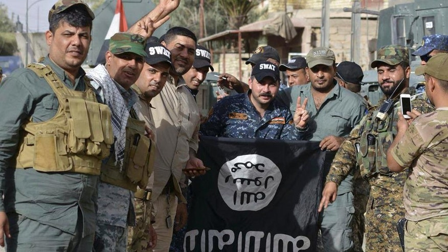 Iraqi security forces celebrate as they pose with a flag of the Islamic State group they captured in central Fallujah, Iraq, after fight against the Islamic State militants Friday, June 17, 2016. Iraqi special forces entered the center of Fallujah city early Friday, taking over a government complex and a neighborhood that served as a base for the Islamic State group militants after intense fighting. (AP Photo)