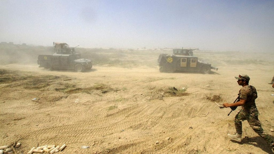 Iraqi security forces advance their positions during the fight against Islamic State militants in Fallujah, Iraq, Wednesday, June 15, 2016. Fallujah has been locked in a cycle of conflict since 2003, when it emerged as a bastion of the insurgency against the U.S. Militant attacks and bombings were followed by sweeping arrest raids, which further stoked local grievances. In 2004, U.S. troops launched two massive assaults on the city, where they fought their bloodiest battles since Vietnam. (AP Photo/Anmar Khalil)
