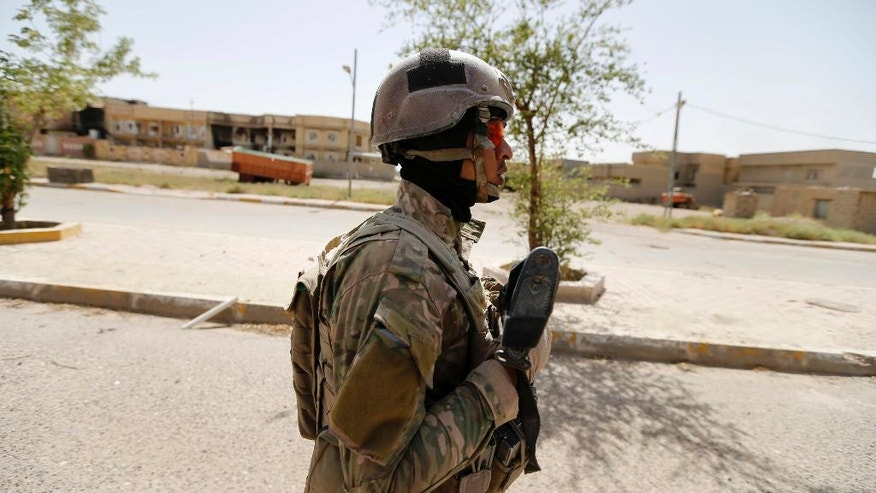 An Iraqi soldier patrols in central Fallujah after fight against the Islamic State militants, Iraq, Friday, June 17, 2016. Iraqi special forces entered the center of Fallujah city early Friday, taking over a government complex and a neighborhood that served as a base for the Islamic State group militants after intense fighting. (AP Photo)