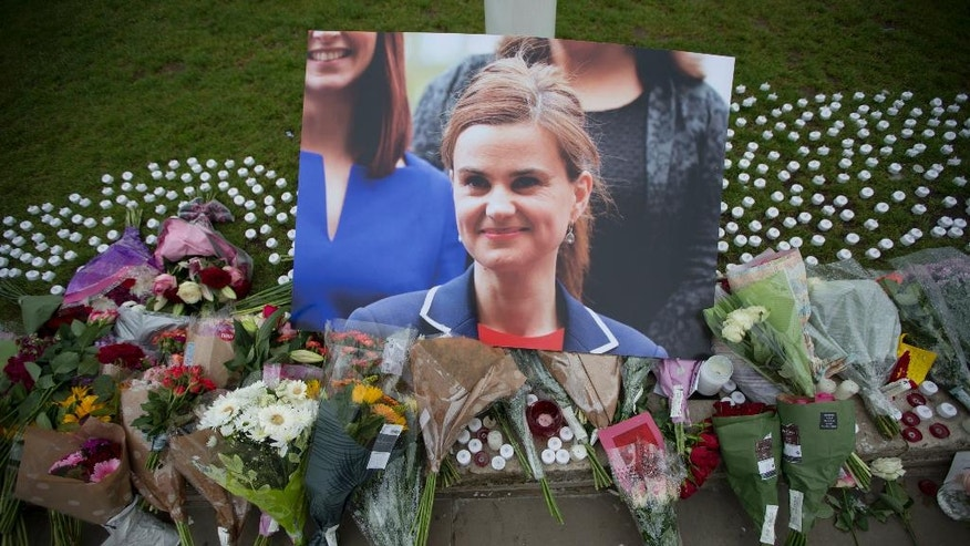 An image and floral tributes for Jo Cox, lay  on Parliament Square, outside the House of Parliament in London, Friday, June 17, 2016, after the 41-year-old British Member of Parliament was fatally injured Thursday in northern England. The mother of two young children was shot to death Thursday afternoon in her constituency near Leeds. A 52-year-old man has been arrested but has not been charged. He has been named locally as Tommy Mair. (AP Photo/Matt Dunham)